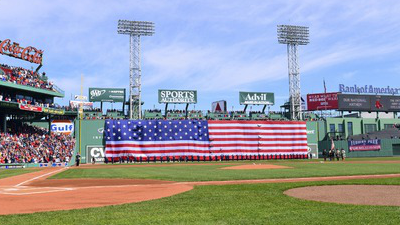 An American flag is unfurled over the Green Monster at Fenway