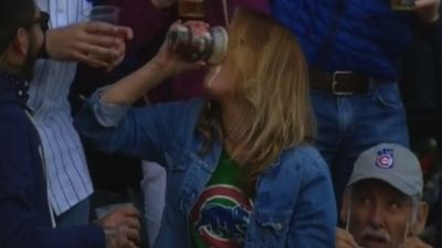 Cubs fan catches a ball in her beer