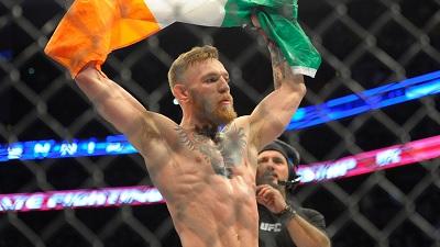 Conor McGregor raises the Irish flag in the octagon.
