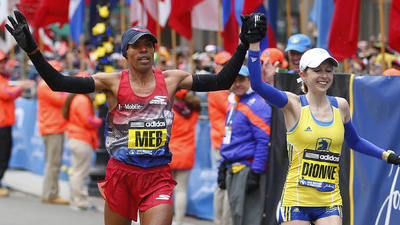 Meb Keflezighi of San Diego, California, holds up the arm of Hilary Dionne of Charlestown, Mass.