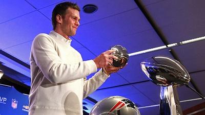 New England Patriots quarterback Tom Brady poses with the Pete Rozelle trophy