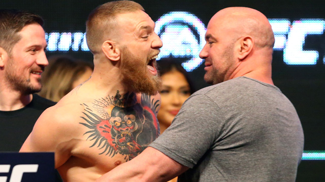 Conor McGregor (left) is held back by UFC president Dana White