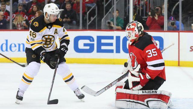 Boston Bruins center David Krejci and New Jersey Devils goaltender Cory Schneider