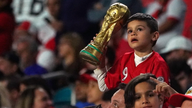Young Peru fan holds a replica of the FIFA World Cup trophy