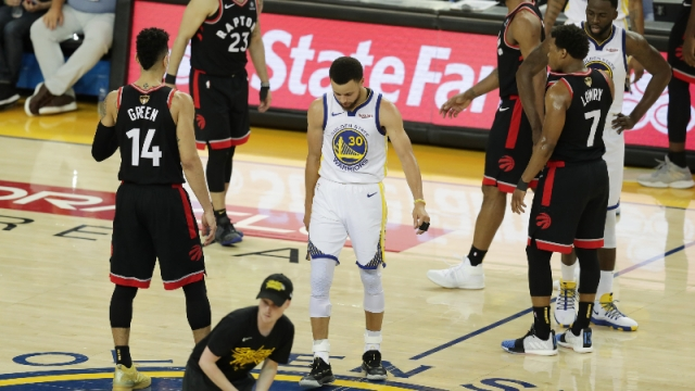 Golden State Warriors guard Stephen Curry and Toronto Raptors players