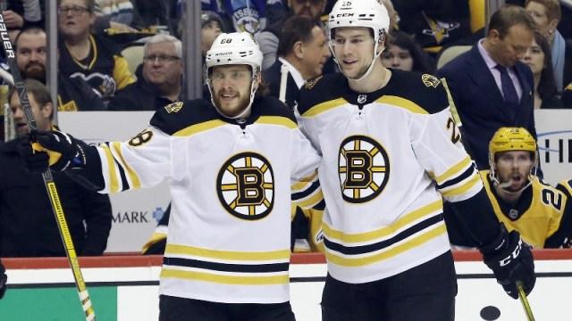 Boston Bruins right wing David Pastrnak (left) and defenseman Brandon Carlo (right)