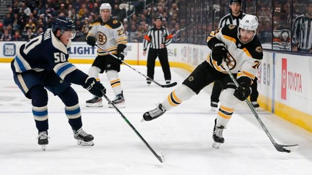 Boston Bruins left wing Jake DeBrusk (74) and Columbus Blue Jackets left wing Eric Robinson (50)