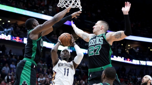 Boston Celtics guard Jaylen Brown (7) and center Daniel Theis (27) and New Orleans Pelicans guard Jrue Holiday (11)