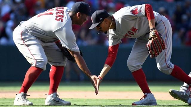 Boston Red Sox third baseman Rafael Devers (11) and right fielder Mookie Betts (50)