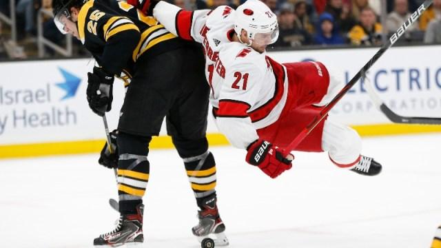 Boston Bruins defenseman Brandon Carlo (25) and Carolina Hurricanes left wing Nino Niederreiter (21)