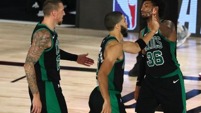 Boston Celtics center Daniel Theis (left), forward Jayson Tatum (center) and guard Marcus Smart