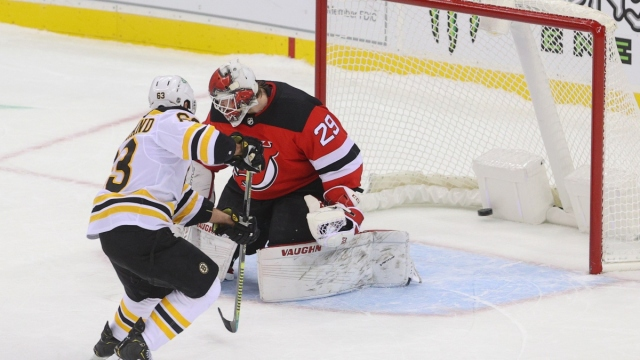 Boston Bruins left wing Brad Marchand (63) and New Jersey Devils goaltender Mackenzie Blackwood (29)