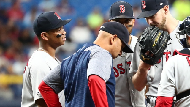 Boston Red Sox manager Alex Cora (front), third baseman Rafael Devers (left) and pitcher Chris Sale (right)