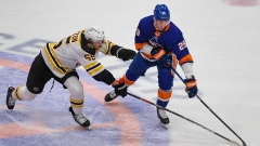Boston Bruins defenseman Jeremy Lauzon (55) and New York Islanders center Brock Nelson (29)