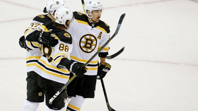 Boston Bruins left wing Brad Marchand (left), right wing David Pastrnak (left) and center Patrice Bergeron (left)