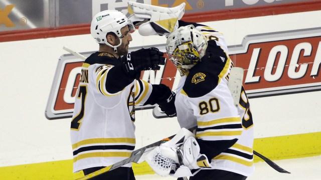 Boston Bruins goalie Dan Vladar, center Patrice Bergeron