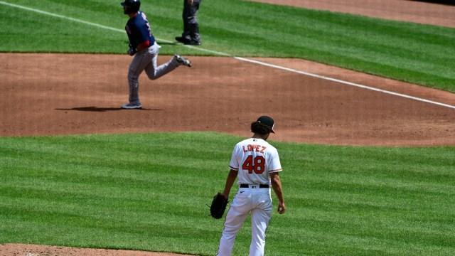 Boston Red Sox designated hitter J.D. Martinez (28) and Baltimore Orioles pitcher Jorge Lopez (48)