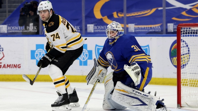 Boston Bruins left wing Jake DeBrusk (74) and Buffalo Sabres goaltender Dustin Tokarski (31)