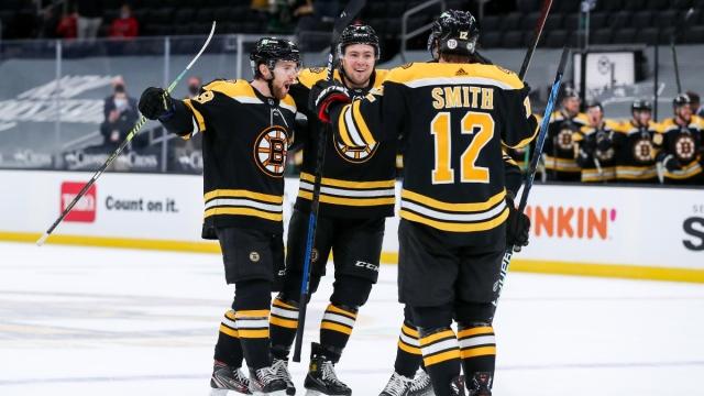 Boston Bruins defenseman Matt Grzelcyk (left), defenseman Charlie McAvoy (73) and center Craig Smith (12)