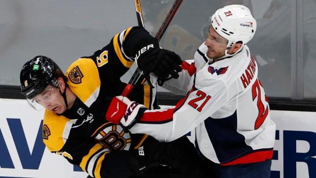 Washington Capitals right wing Garnet Hathaway (21) and Boston Bruins defenseman Mike Reilly (6)