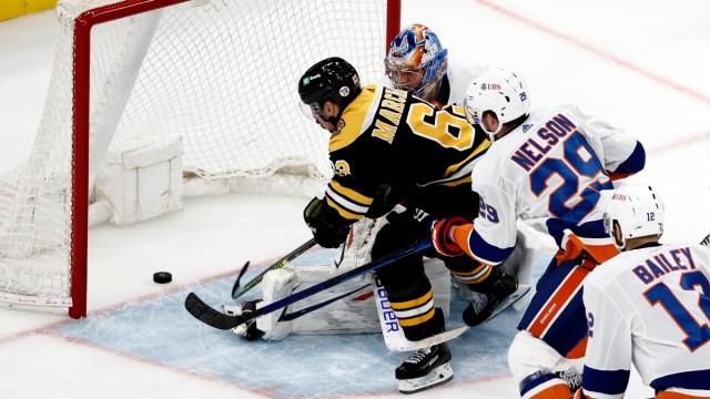Boston Bruins left wing Brad Marchand (63), and New York Islanders goaltender Semyon Varlamov (40)