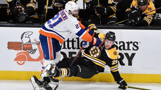 New York Islanders right wing Kyle Palmieri (21) and Boston Bruins defenseman Brandon Carlo (25)