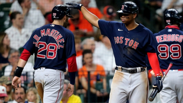 Boston Red Sox designated hitter J.D. Martinez (28) and third baseman Rafael Devers (11)