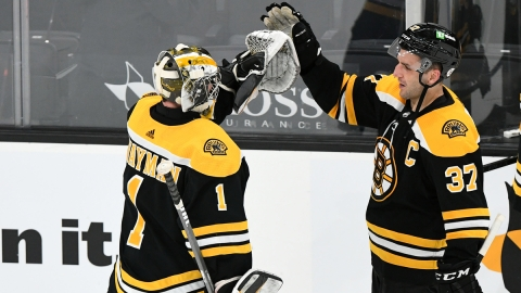 Boston Bruins goalie Jeremy Swayman, center Patrice Bergeron